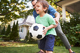 Father Playing Soccer In Garden With Son