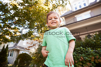 Portrait Of Young Boy Playing In Garden At Home