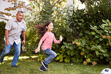Grandfather Playing Soccer In Garden With Granddaughter