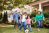 Multi Generation Family Playing Soccer In Garden