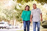Senior Couple Walking Along Suburban Street Holding Hands
