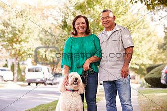 Portrait Of Senior Couple Walking Dog Along Suburban Street