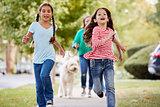 Grandmother And Granddaughters Walking Dog Along Suburban Street