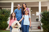 Portrait Of Family Standing in Front Of House With Pet Dog