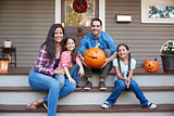 Portrait Of Family Carving Halloween Pumpkin On House Steps