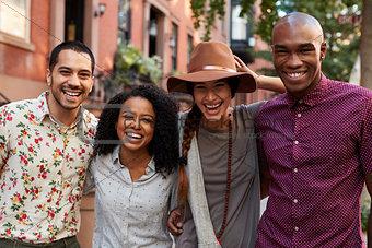Portrait Of Friends Walking Along Urban Street In New York City