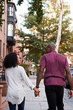 Rear View Of Couple Walking Along Urban Street In New York City