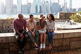 Friends Visiting New York With Manhattan Skyline In Background