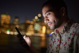 Man Using Mobile Phone At Night With City Skyline In Background