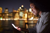 Woman Uses Mobile Phone At Night With City Skyline In Background