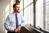 Senior businessman in shirt and tie looking out of window