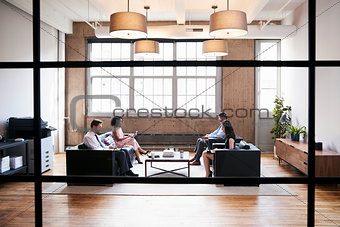 Business people in lounge meeting area, seen through window