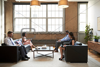 Business people using laptops in a lounge meeting area