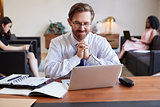 Businessman using laptop at desk, colleagues in background