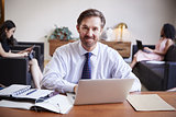 Businessman using laptop at desk smiling to camera