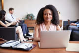 Young black businesswoman working at a desk looks to camera