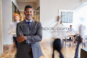 Portrait of middle aged black man in a busy modern workplace