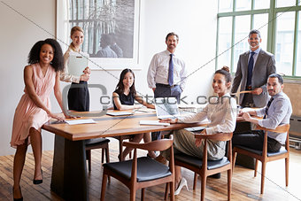 Young professionals at business meeting turn to face camera