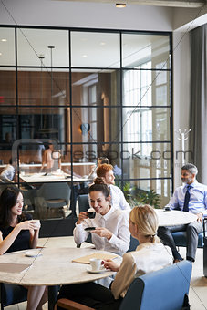 Business colleagues relaxing at their office cafe, vertical