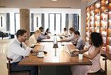 Colleagues at desks in a busy open plan office, close up