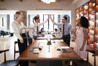 Four colleagues celebrating success in an open plan office