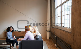 Three colleagues at a casual work meeting in a lounge area