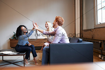Three colleagues high five at a casual work meeting