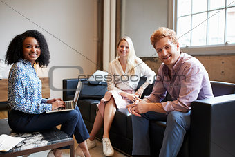 Three young colleagues at a casual work meeting look to camera