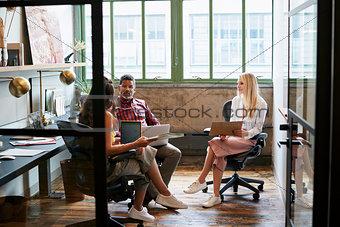 Three coworkers in a team meeting, seen through open door