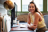 White woman at a computer in an office smiling to camera