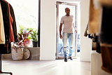 Young black man walking into a clothes shop and closing door