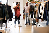 Customer holds up clothes in a shop while assistant looks on