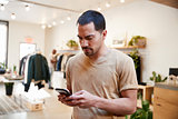 Young Hispanic man using smartphone in a clothes shop