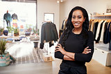 Young black woman smiling to camera in a clothes shop