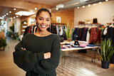 Young Hispanic woman smiling to camera in a clothes shop