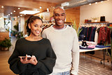 Young adult couple smiling to camera in a clothes shop