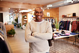 Young black man smiling to camera in a clothes shop