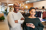 Young couple with tablet smiling to camera in clothes shop