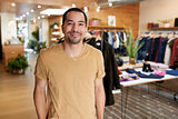 Smiling young Hispanic man standing in a clothes shop