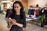 Young black woman using tablet computer in a clothes shop