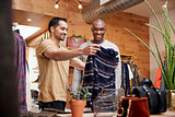 Two young men holding up clothes to look at in clothes shop