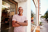 Young black man smiling to camera outside his clothes shop