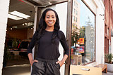 Young black woman smiling to camera outside her clothes shop