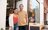 Young Hispanic couple smiling to camera outside their shop