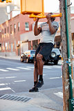 Young black man doing chin ups in Brooklyn street, vertical