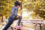 Young black woman stretching on a bench in a Brooklyn park