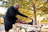 Young black man stretching leg in a Brooklyn park