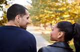 Young Hispanic couple walking in Brooklyn park, back view