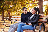 Young Hispanic couple sitting on bench in Brooklyn park