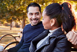 Young couple sitting on bench in Brooklyn park, close up
